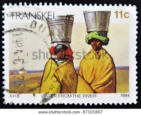 REPUBLIC OF SOUTH AFRICA - CIRCA 1984: A stamp printed in Transkei shows Women fetching water from the river on their heads, circa 1984