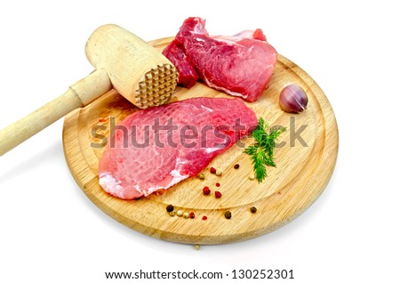 Repulsed a piece of meat, garlic, pots of different peppers, fennel, wooden mallet on a circular wooden board isolated on white background
