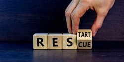 Rescue and restart symbol. Businessman hand turns cubes and changes the word 'rescue' to 'restart'. Beautiful dark grey background. Business and rescue - restart concept. Copy space.