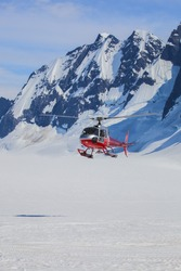 rescue helicopter flying low over a snowy glacier.