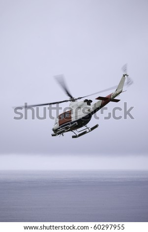 Rescue Helicopter flying over sea - stock photo