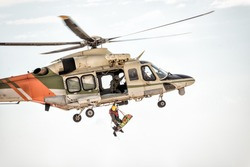 Rescue helicopter in flight winching rescuer.