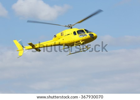 Rescue helicopter. Yellow helicopter flying over the terrain.