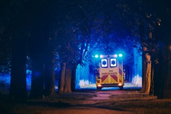 Rescue in dark alley. Rear view of ambulance of emergency medical service against illuminated trees from blue flasher.