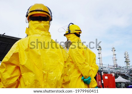 Rescue personnel wear yellow chemical protective clothing during chemical spill recover as part of emergency drills at chemical plant. Stok fotoğraf ©