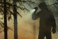 Rescue Search. Men Wearing Camouflage Clothing with Powerful Flashlight Between Trees and Fire Smoke. Forest Wildfire Rescue Mission.