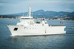 Rescue ship white French Navy. A French military rescue vessel underway in a bay off the coast of France.