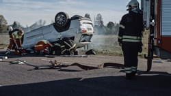 Rescue Team of Firefighters and Paramedics Work on a Terrible Car Crash Traffic Accident Scene. Preparing Equipment, Stretches, First Aid. Saving Injured and Trapped People from the Burning Vehicle
