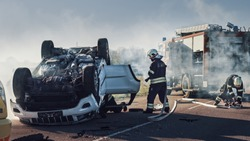 Rescue Team of Firefighters Arrive on the Car Crash Traffic Accident Scene on their Fire Engine. Firemen Grab their Equipment, Prepare Fire Hoses and Gear from Fire Truck.