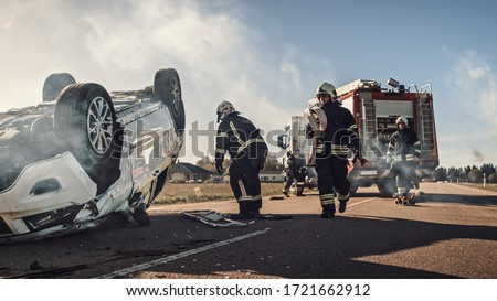 Rescue Team of Firefighters Arrive on the Car Crash Traffic Accident Scene on their Fire Engine. Firemen Grab their Tools, Equipment and Gear from Fire Truck, Rush to Help Injured, Trapped People