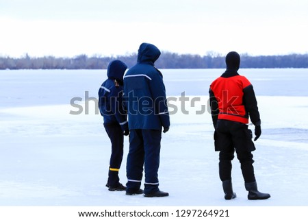 Rescuers in uniform and diving suit are on duty on the ice of a frozen river during winter fishing and sport events. Rescue service on the Dnieper River, Dnipro city, Ukraine, Dnepropetrovsk #1297264921