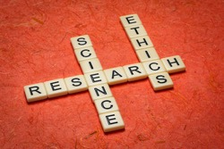 research and science ethics - crossword in ivory letters against textured handmade bark paper