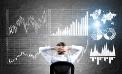 Research concept with businessman sitting in front of wall with forex charts