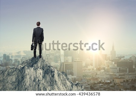 Research concept with businessman standing on mountain top and looking at sun setting over city Foto d'archivio ©