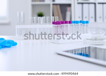 Research laboratory working space. Test tubes and tablet PC are lying at the table. Medical equipment. Blood test