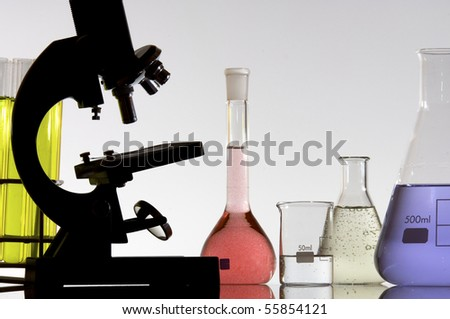 research microscope and laboratory bottles with colored liquid - stock photo