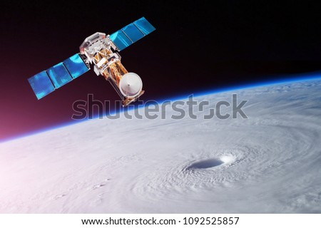 Stock Photo Research, probing, monitoring of tracking in a tropical storm zone, a hurricane. Satellite above the Earth makes measurements of the weather parameters. Elements of this image furnished by NASA