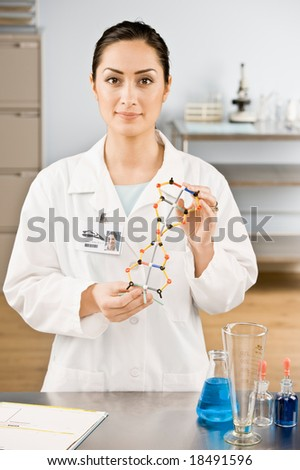 Research scientist holding molecular model in laboratory
