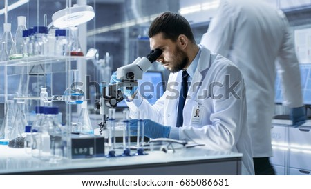 Research Scientist Looks into Microscope in Research Centre. He's Conducts Experiments in Modern Laboratory.