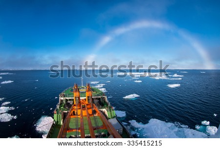 Research ship going under white rainbow through the ice in Arctic ice in East-Siberian sea, Arctic ocean. White rainbow is rare meteorological phenomenon.