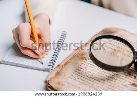 Researcher examines antique book with magnifying glass. Scientific translation of ancient literature. Studying manuscript with ancient writings. High quality