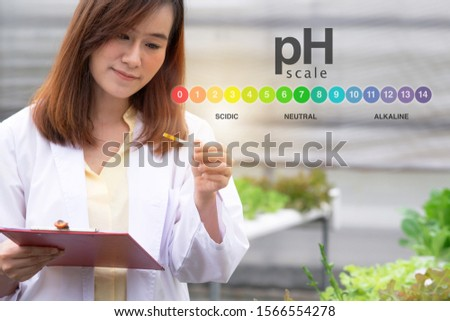 Researcher in white uniform are checking with ph strips in hydroponic farm, and pH level scale graphic, science and research concept