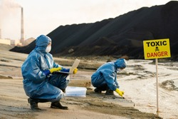Researcher in workwear describing characteristics of polluted water and soil on background of colleague taking samples in toxic area