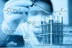 researcher is testing, dropping reagent to test tube at laboratory with chemical equations and periodic table background.Man wears protective goggles