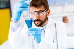 Researcher working with blue liquid at separatory funnel in the laboratory
