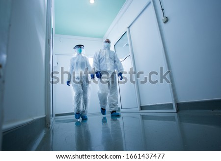 Researchers in protective clothing walking through laboratory hall. Virus and diseases safety concept Stock photo ©