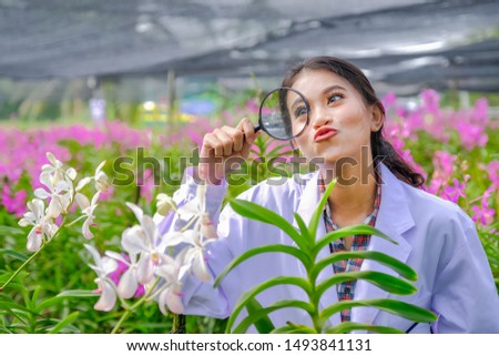 Researchers, young women, wearing white dresses, checking orchids and recording changes to improve orchid species