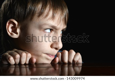 resentful young boy on a black background