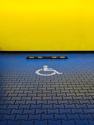 Reserved blue car parking space for handicapped people. International disabled symbol painted in a shopping center parking lot.