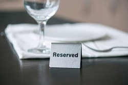 Reserved iron sign on wooden table in front of white tablecloth and wine glass at a cafe or restaurant