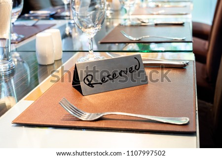 Reserved Metal Plate on the Table with Blurry background. Reservation Seat at restaurant.