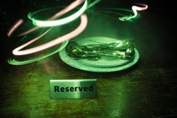 Reserved sign on the table. A tag of reservation placed on the wood table. Metal tag with reservation on dark. Reserved table in a restaurant. Creative concept with colorful lights. Selective focus