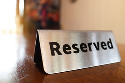 Reserved sign on top of a wooden table in a restaurant, Reservation seat at restaurant for dating on celebrate day concept(select focus).