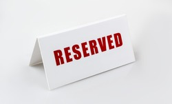 Reserved sign standing on the white background. Letters are red.