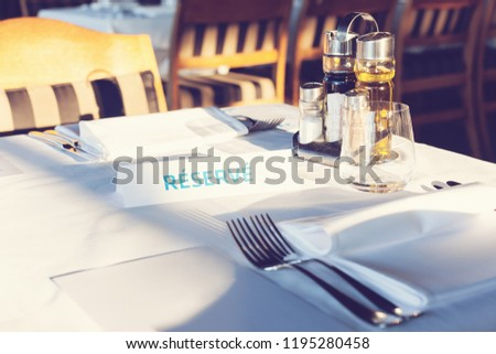 Reserved Table. A tag of reservation placed on the wood table. Reserved logo. Reservation sign. Paper tag with reservation logo. Reserved table in a restaurant.