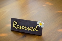 Reserved table sign with places at wood table in restaurant or coffee shop, club, bar for breakfast or lunch or dinner. Selective focus concept.