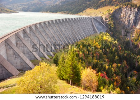 reservoir in the Alps is known for its large, high concrete dam. Aerial morning view of Roselend lake/Lac de Roselend. Picturesque autumn scene of Auvergne-Rhone-Alpes, France, Europe. #1294188019
