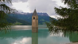 Reservoir Reschensee, South Tyrol, Italy with lone standing steeple in the water, the remaining of flooded village Graun, in early summer with low water level.