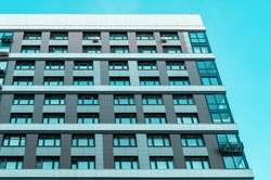 Residental monolithic building and condominium on blue sky background. Residential neighborhoods of the city in the day light. Apartments facade and cyan sky.
