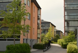 Residential apartment housing in the cosy neighbourhood called Tuomarila in Espoo, Finland. Modern Scandinavian architecture with different color buildings surrounded by trees and walking paths.
