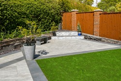 Residential back garden landscaped with light and dark grey porcelain paving slabs and artificial grass. No people.