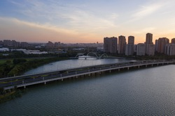 Residential buildings and overpass bridge by the lake. Photo in Suzhou, China.
