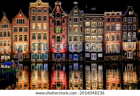 Residential buildings are reflected in the night water. River channel houses in night lights. Night reflection in water. City houses reflected in water in night