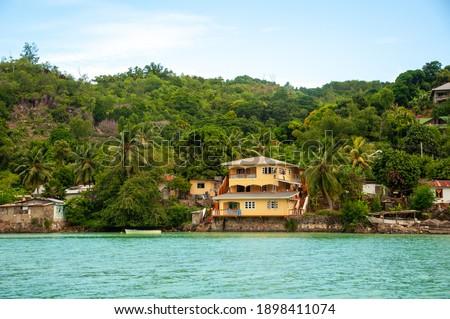 Residential buildings seen through wavy waters on background of mountain foli Stock fotó ©
