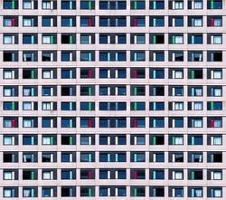 Residential cells of the hostel building. Modern minimalistic architecture with a lot of square glass windows and colors on the building. The rhythm of the windows. Geometric pattern.
