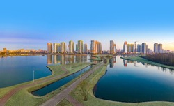 Residential complex on the shore of the lake. Modern urban architecture. Apartments in new buildings near the recreation area. Urban landscape. Ponds and houses under a blue sky.